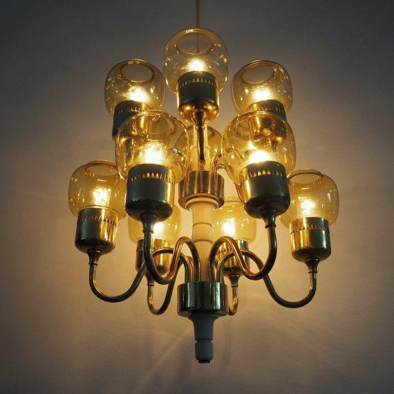Hans Agne Jakobsson Chandelier - brass met 12 amberkleurige glazen en twee reserve glazen - deze zijn alle 14 gaaf, het messing heeft wat patina -H 68cm incl. messing plafondkap - €650